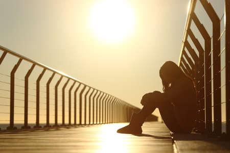 jeune fille adolescente: Sad teenager girl déprimé assis dans le plancher d'un pont sur la plage au coucher du soleil