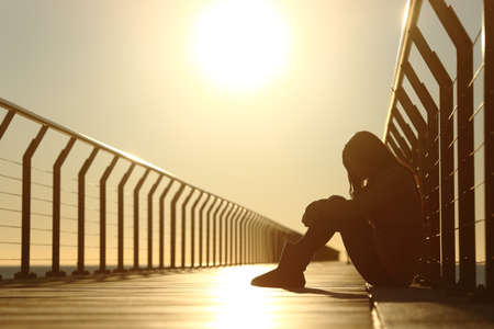 Sad teenager girl depressed sitting in the floor of a bridge on the beach at sunset Stok Fotoğraf - 37323210