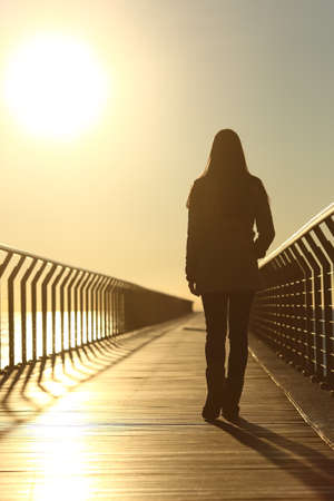 Sad woman silhouette walking alone on a bridge on the beach in winter at sunset