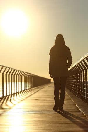 walking alone: Silueta de mujer triste caminando solo en un puente en la playa en invierno al atardecer