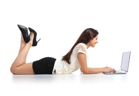 faldas: Mujer atractiva que miente trabajar con un ordenador portátil aislados en un fondo blanco Foto de archivo