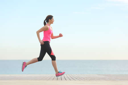run woman: Side view of a woman running on the beach with the horizon and sea in the background