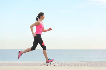 corriendo: Vista lateral de una mujer corriendo en la playa con el horizonte y el mar en el fondo Foto de archivo
