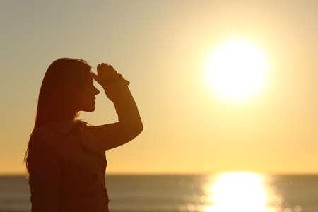 mujer mirando el horizonte: Vista lateral de una silueta de una mujer mirando hacia adelante en la puesta de sol en la playa