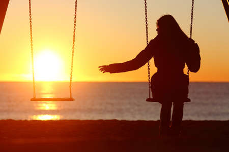 love sad: Single or divorced woman alone missing a boyfriend while swinging on the beach at sunset