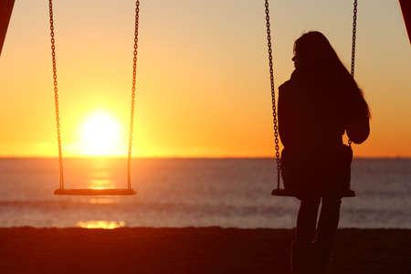 novios enojados: Swinging sola mujer sola en la playa y mirar hacia otro asiento falta un novio