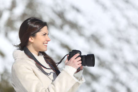 Tourist woman photographing on winter holidays with a snowy mountain in the background photo
