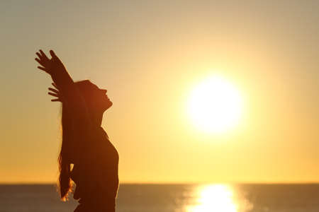 Woman breathing fresh air at sunset on the beach and raising arms