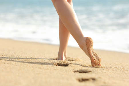 feet naked: Woman legs and feet walking on the sand of the beach with the sea water in the background
