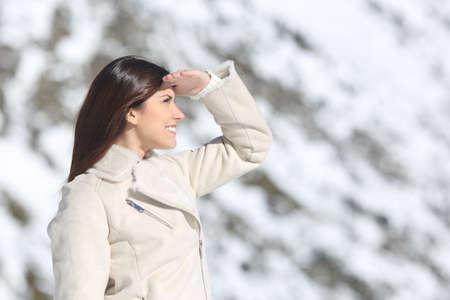 mujer mirando el horizonte: Mujer que mira adelante con la mano en la frente, en las vacaciones de invierno con una montaña nevada en el fondo