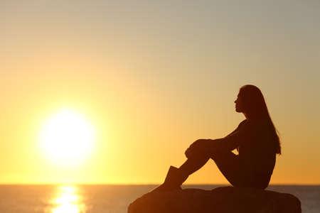 mujer mirando el horizonte: Perfil de una silueta mujer viendo el sol en la playa al atardecer