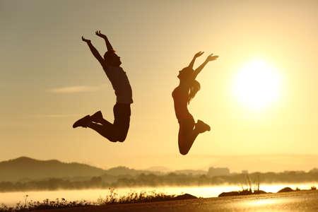 horizonte: Pares de la aptitud que salta feliz al atardecer con el sol en el fondo Foto de archivo