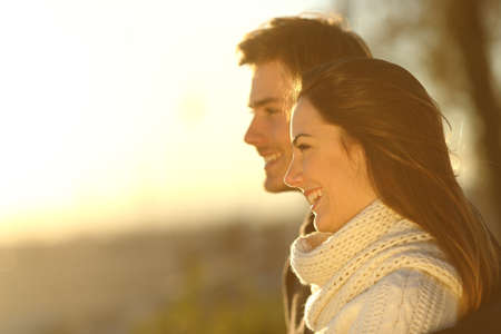 horizons: Side view of a happy couple looking at sunset in winter on the beach Stock Photo