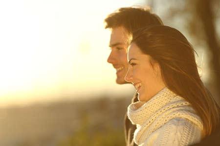 mujer mirando el horizonte: Vista lateral de una pareja feliz mirando la puesta de sol en invierno en la playa Foto de archivo