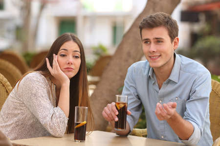 Man and woman dating in a restaurant terrace but she is boring while he speaks Standard-Bild
