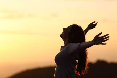 Terug licht van een vrouw ademhaling verhoging van de armen met een warme achtergrond Stockfoto
