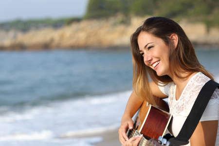 背景に海とビーチでギターを弾くギタリストの美しい女性