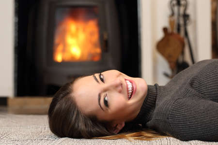 Beauty woman with perfect smile resting on the floor at home with a fireplace in the background