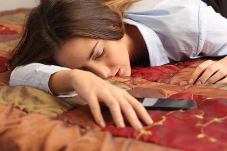 durmiendo: Close up retrato de una mujer de negocios cansado y dormir en una cama de hotel con un teléfono móvil Foto de archivo