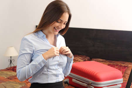 Businesswoman traveler undressing in a hotel room after a business travel photo