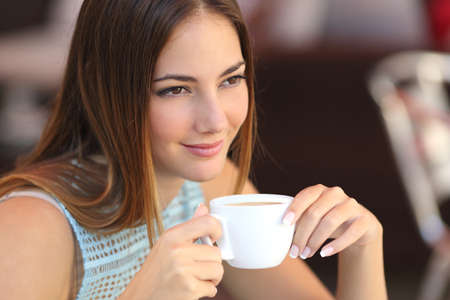 Candid woman thinking in a coffee shop holding a cup with an unfocused background photo