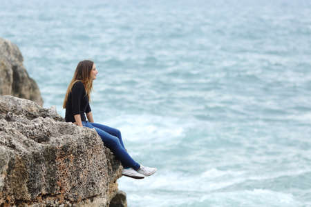 Side view of a full body of a casual woman thinking sitting in a cliff watching the sea 版權商用圖片