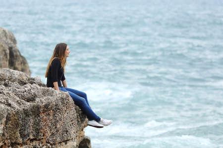 women thinking: Vista lateral de un cuerpo completo de un pensamiento casual mujer sentada en un acantilado mirando el mar