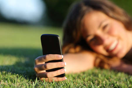 Close up of a happy teen girl hand using a smart mobile phone resting on the grass photo