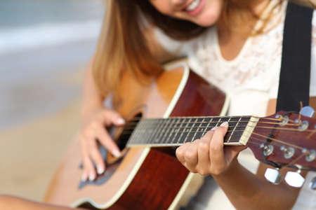 夏の晴れた日のビーチでギターを弾く女性のクローズ アップ