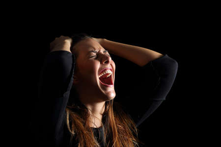 Depressed woman crying and shouting desperately isolated in a black background Stock Photo