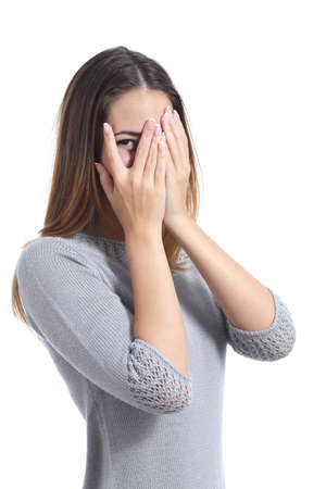 Embarrassed woman looking through her hands covering her face isolated on a white background