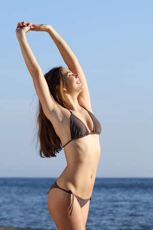 axila: Cuerpo Fitness mujer posando de pie en la playa con el mar de fondo