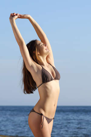 underarms: Fitness woman body posing standing on the beach with the sea in the background Stock Photo