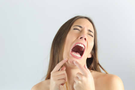 grimace: Girl crying while pressing a pimple on her chin with a grey background Stock Photo