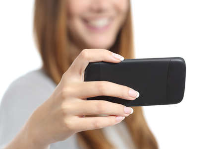 Girl watching media videos on a smart phone isolated on a white background photo