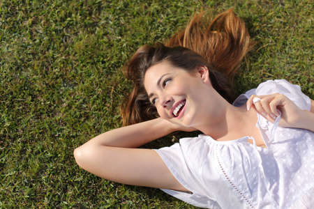 descansando: Vista superior de una mujer relajada feliz acostado en la hierba verde y mirando el lado sonriendo Foto de archivo