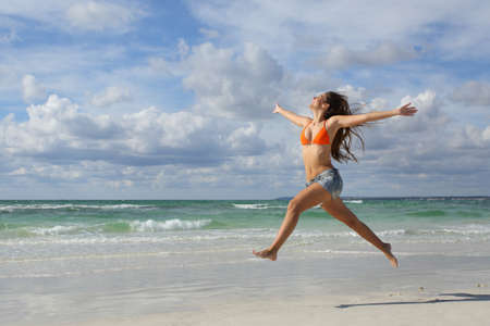 Happy woman jumping and running on the beach on holidays with a cloudy sky in the background