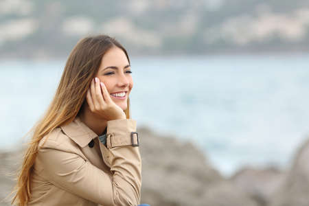 girl thinking: Portrait of a happy woman thinking and looking away on the sea with an unfocused background