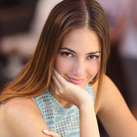 Portret van een zelfverzekerde vrouw met een perfecte huid op zoek naar camera met een ongericht achtergrond Stockfoto