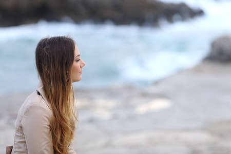 mujer pensativa: Perfil de una mujer pensativa seria en la playa en invierno mirando a otro lado