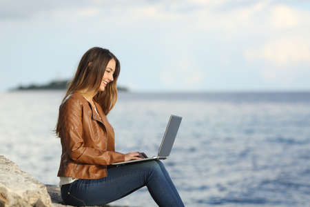 self employed: Profile of a self employed woman working with a laptop on the beach with the sea in the background