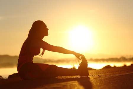 夕暮れをバック グラウンドで太陽のストレッチ フィットネス女性のシルエット