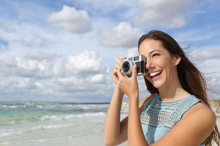 taking photograph: Happy tourist photographer girl taking photo in holidays with a cloudy sky and the sea in the background Stock Photo