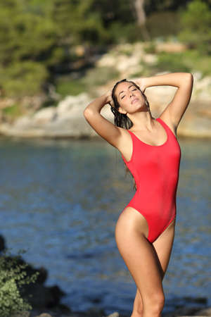 armpits: Woman posing wearing a red swimsuit on the beach hair removal concept