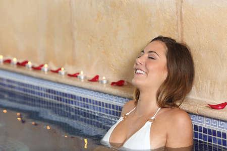 mujer ba�andose: Ba�o de la mujer y relajantes feliz en un jacuzzi spa con velas y p�talos de rosa