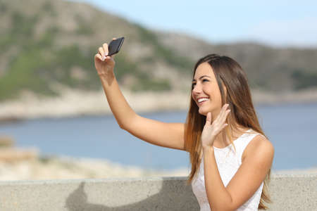 Casual elegant woman greeting with her hand while photographing a selfie with a smartphone on the beach photo