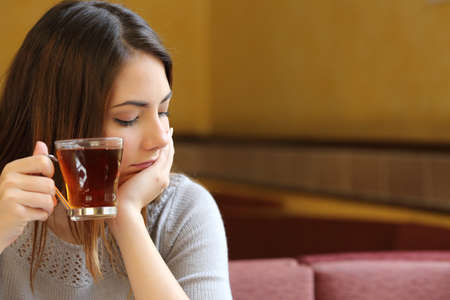 若い女性は茶と思考のカップを保持しているコーヒー ショップに座ってリラックスしてください。