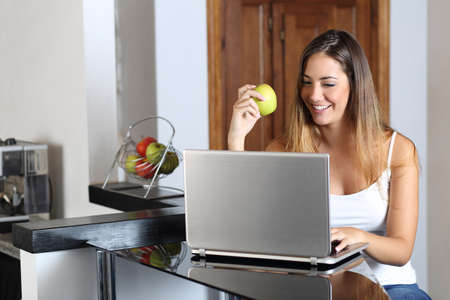 home computer: Entrepreneur woman browsing a laptop and eating at home in the kitchen