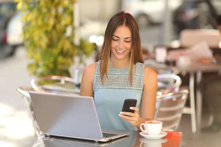 幸せな起業家、通りのコーヒー ショップでノート パソコンと携帯電話の操作