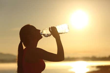 バック グラウンドで太陽と日没でボトルからフィットネス女性シルエット飲料水のプロファイル